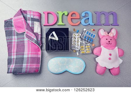Word Dream with pajamas, little toy and pills on a grey background