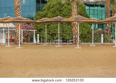 Straw sunshades sand beach on hotel with green glass walls background
