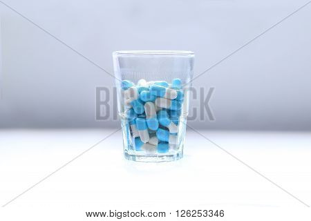 Blue pills capsules pills in a glass. taking too much medication Health concept.