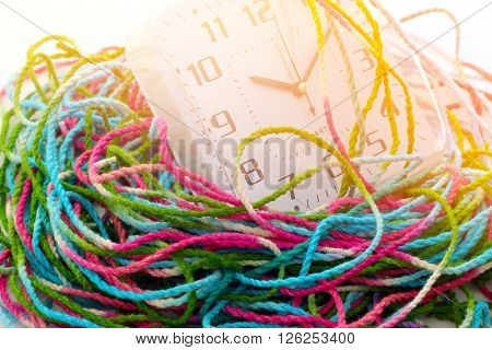 Busy time clock is wrap with tangled yarn time concept