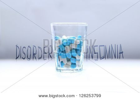 Blue pills capsules pills in a glass taking too much medication Health concept