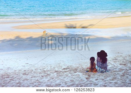 Mother and daughter sitting at the beach on hoiday