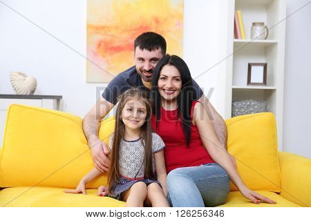 Family sitting on the yellow sofa.
