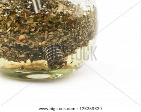 Glass mate calabash vessel filled with a mate tea and bombilla drinking straw inside it, composition isolated over the white background, close-up crop fragment as a copyspace backdrop