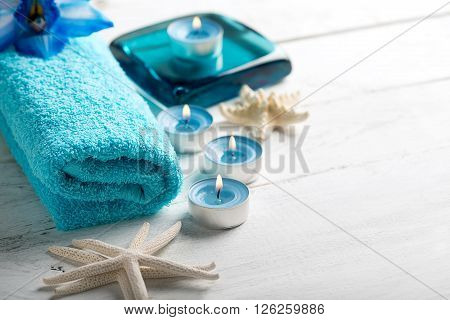 SPA still life with towel candles and starfish on white wooden surface