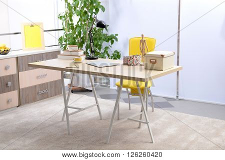 Workplace with table, yellow chair and laptop in living room