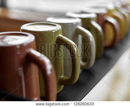 Black shelf lined with multi colored ceramic coffee mugs