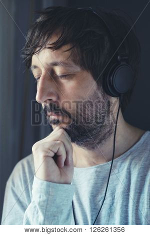 Unshaven adult man listening to music on headphones by the window enjoy favorite song with his eyes closed.