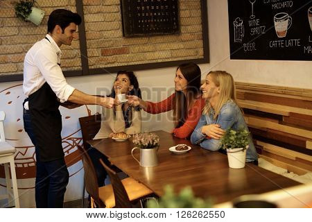 Pretty girls served by young waiter in cafeteria, smiling happy.