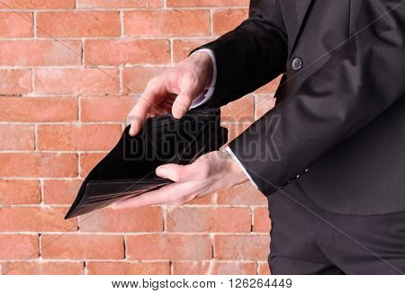 Man in a suit showing an empty purse on brick wall background