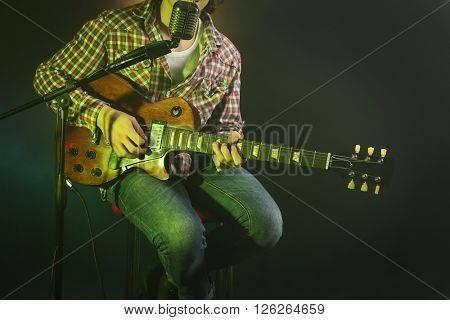 Young man with microphone playing electric guitar on lighted dark background