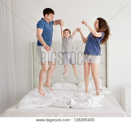 Family of three, young parents and a little son jumping and having fun in bed.