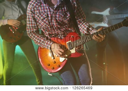 Young group playing electric guitars on lighted foggy background