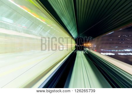 Motion blur of a city and tunnel from inside a moving monorail