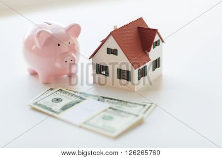 mortgage, investment, real estate and property concept - close up of home or house model, us dollar money and piggy bank