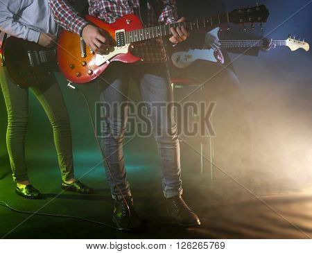 Young group playing electric guitar on lighted foggy background