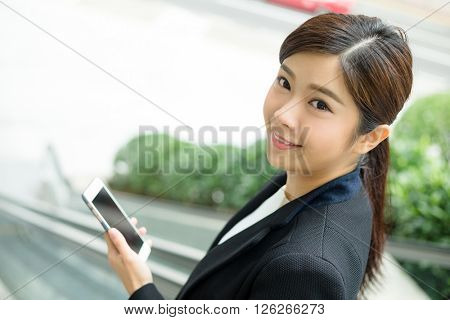 Businesswoman going down to escalator with mobile phone