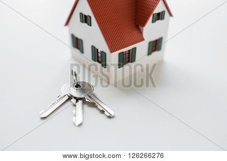 architecture, building, mortgage, real estate and property concept - close up of home model and house keys