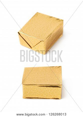 Single bouillon stock broth cube wrapped in golden foil, composition isolated over the white background, set of two different foreshortenings