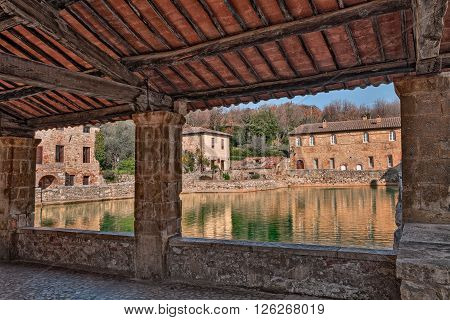 Old thermal baths in the medieval village Bagno Vignoni Siena Tuscany Italy - View from the portico of the Square of sources, spa basin in the ancient italian town