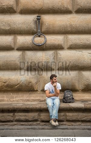 Florence, Italy - September 16, 2015: Unknown man sitting in front of big wall in Florence, Italy