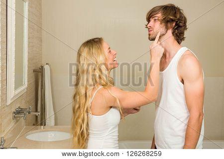 Cute couple applying cream in the bathroom