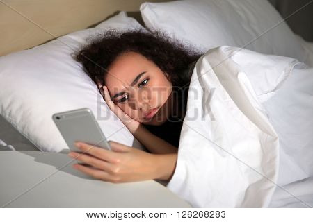 Sleepy girl with cellphone in bed