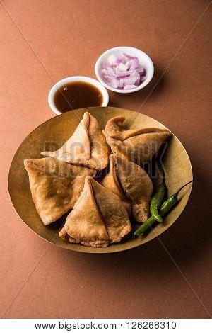 samosa snack with imli chutney or tamarind sauce, onion and green fried chili