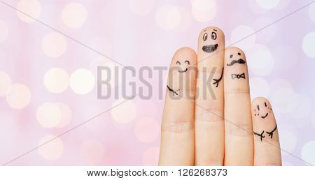 gesture, family, people and body parts concept - close up of four fingers with smiley faces over pink holidays lights background