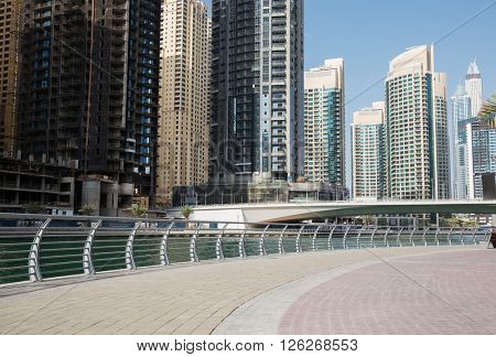 cityscape, travel, tourism and urban concept - Dubai city business district with skyscrapers on seafront and bridge