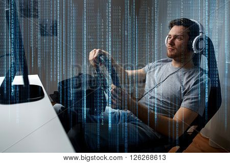 technology, gaming, entertainment and people concept - young man in headphones with pc computer playing car racing video game at home and steering wheel
