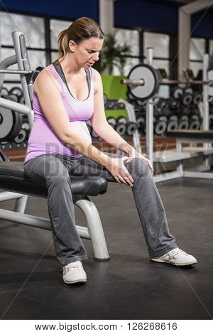 Woman hurting her knee in the gym