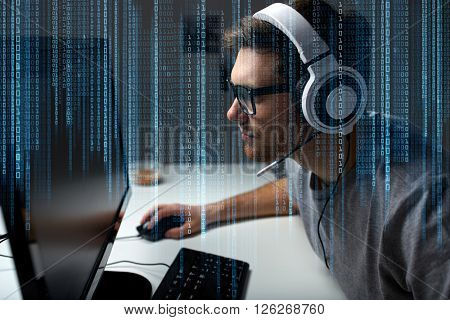 technology, gaming, entertainment, let's play and people concept - young man in headset and glasses with pc computer playing game at home and streaming playthrough or walkthrough video