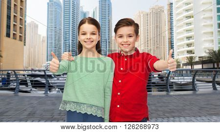 childhood, travel, tourism, gesture and people concept - happy smiling boy and girl hugging and showing thumbs up over dubai city street background
