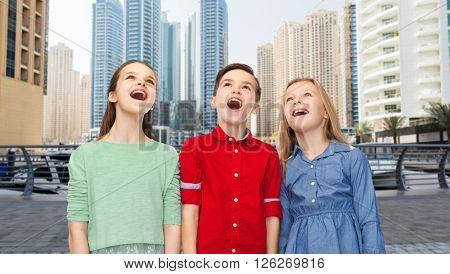 childhood, emotions, travel, tourism and people concept - happy amazed boy and girls looking up with open mouths over dubai city street background
