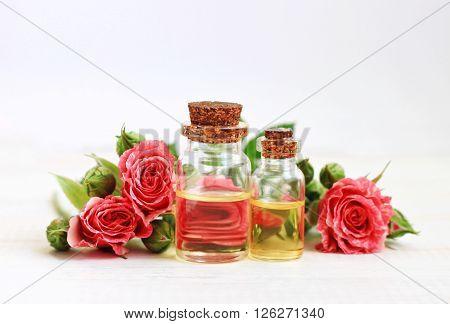 Aromatic essential rose oil in bottles, garden rose flowers.
