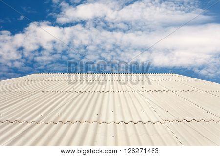 White asbestos slate roof against blue sky