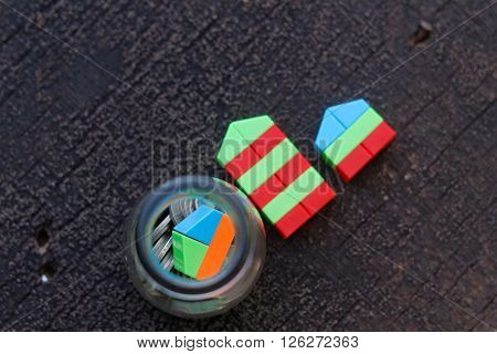 Two replica of house made from plastic block representing a house and apartments beside a jar filled with coins and replica of a house inside the jar. Concept of housing loan,saving for a house.