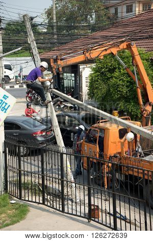 CHIANGMAI THAILAND - APRIL 10: Eletrican climb on old broken power pole to change the new one. They work with crane truck on April 10 2016 in ChiangMai Thailand