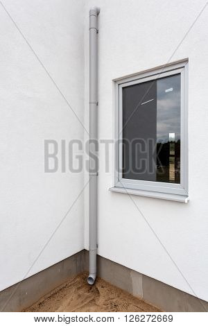 New rain gutter on a white wall with window