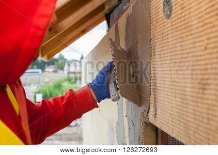Worker plastering a facade of a new house on mineral rockwool panels. Process of insulation of house for better energy efficiency