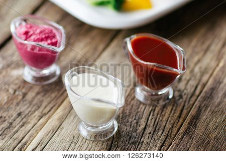 European cuisine.  The variety of sauces: mayonnaise, tomato, horseradish.  Top view on european cuisine  food on wooden background.