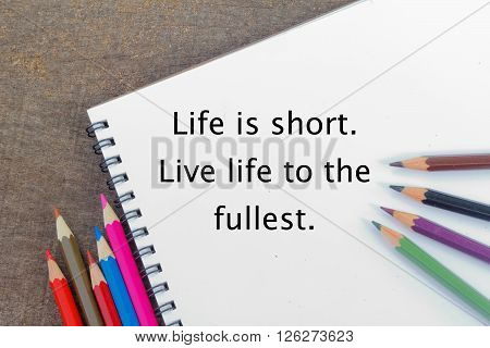 Blank notepad and colorful pencils on the wooden table. View from above. With phrase Life is short. Live life to the fullest.