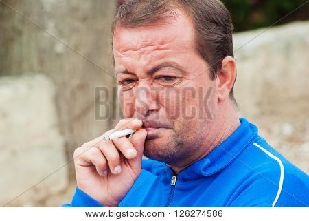 Senior Man Dressed In Formal Clothes Smoking Cigaretes