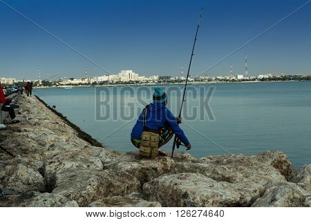 DOHA, QATAR, 15-APRIL-2016: Fisherman is waiting the fish. There are a lot of fishermen tried to catch the fish, but this one did all these preparation so professional that I decided to make a shoot with him. Doha, Qatar. 15 April 2016 6-45 am