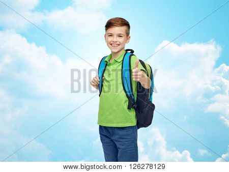 childhood, school, education and people concept - happy smiling student boy with school bag over blue sky and clouds background