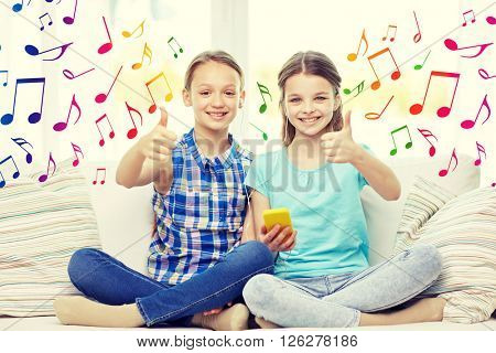 people, children, technology, friends and friendship concept - happy little girls with smartphone and earphones listening to music and showing thumbs up at home over colorful musical notes background