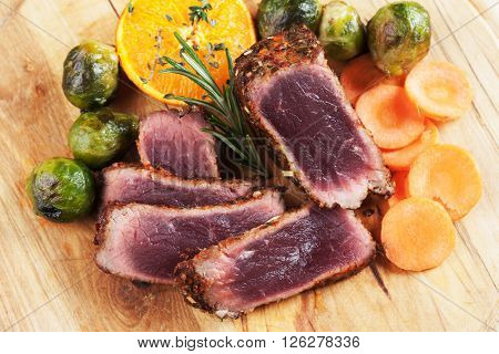 Slices of rare steak with carrot and brussel sprout on wooden board
