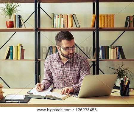 Attractive young businessman with the glasses rewriting from a book and looking at his laptop