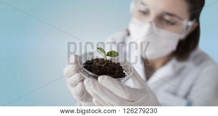 science, biology, ecology, research and people concept - close up of young female scientist wearing protective mask holding petri dish with plant and soil sample over blue background